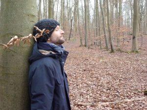 Foto: Mann mit geschlossenen Augen lehnt an Buche